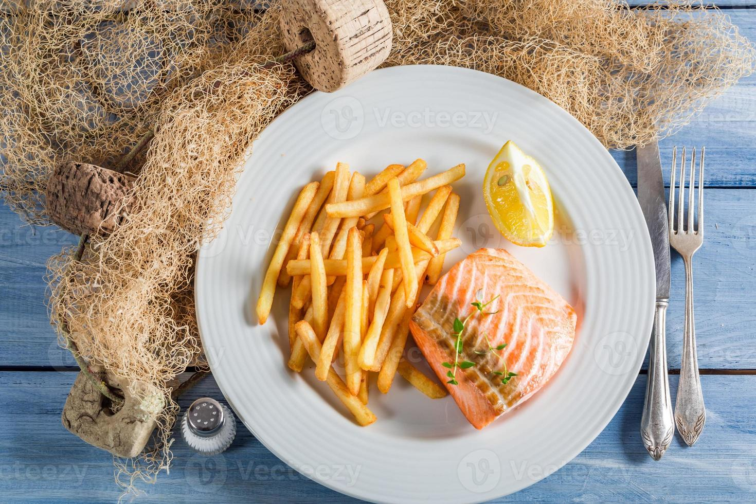 Delicious french fries with salmon served on plate photo