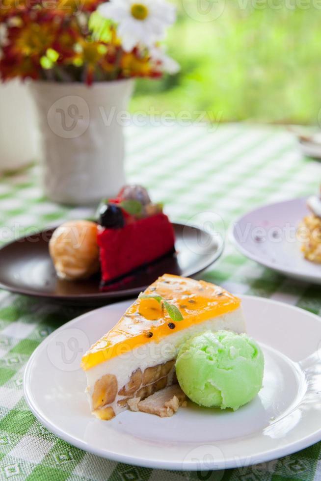 tarta de queso y helado en plato con cobertura de fruta. foto