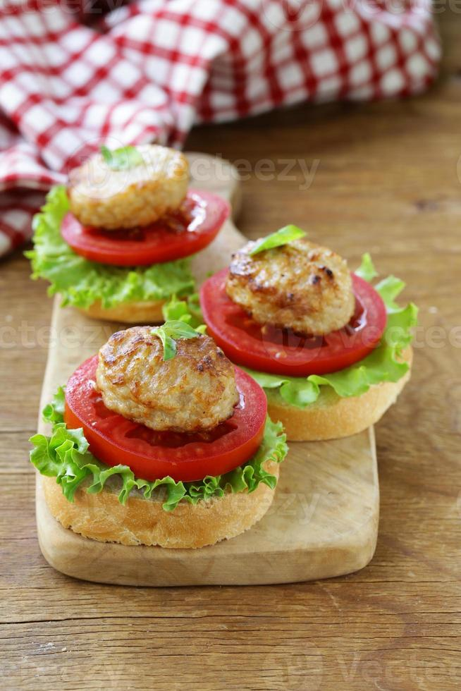 appetizer mini burgers with tomatoes, lettuce and meat balls photo