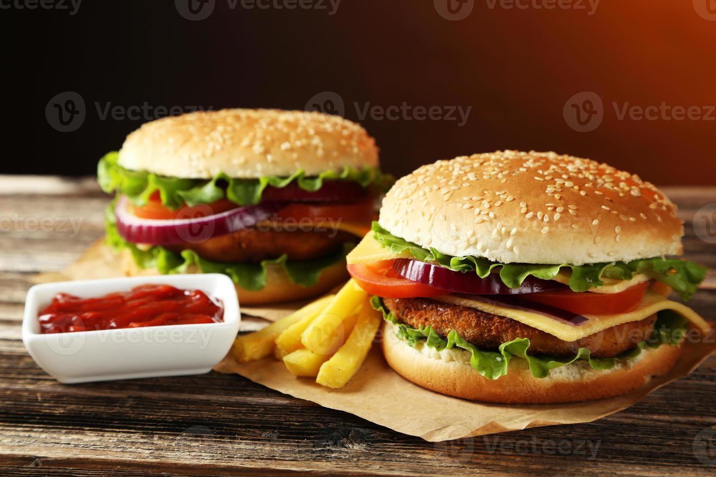 immagine di 2 hamburger su un tavolo di legno con patatine fritte e ketchup foto