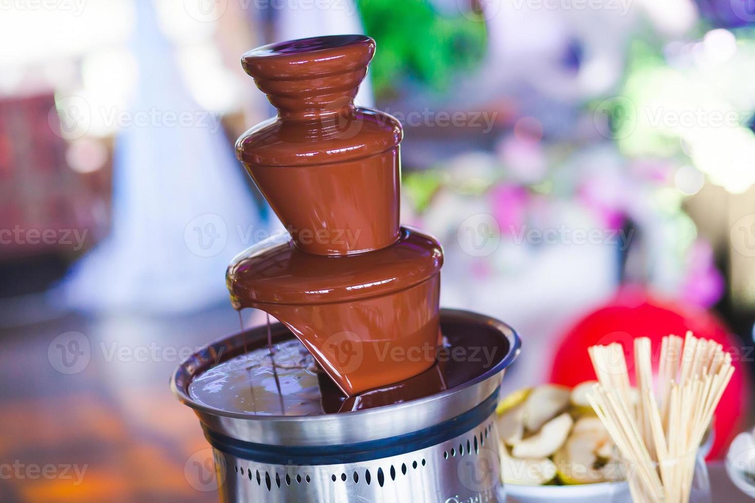 Fuente de chocolate con fondue, frutas y malvaviscos en fiesta infantil foto