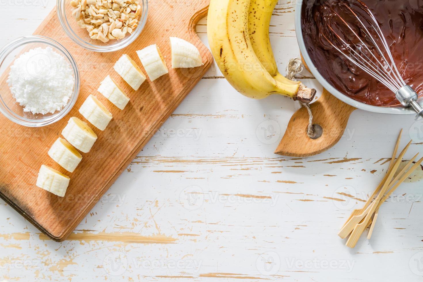 preparación de paletas de plátano: plátano, chocolate, nueces, coco en polvo, palos foto
