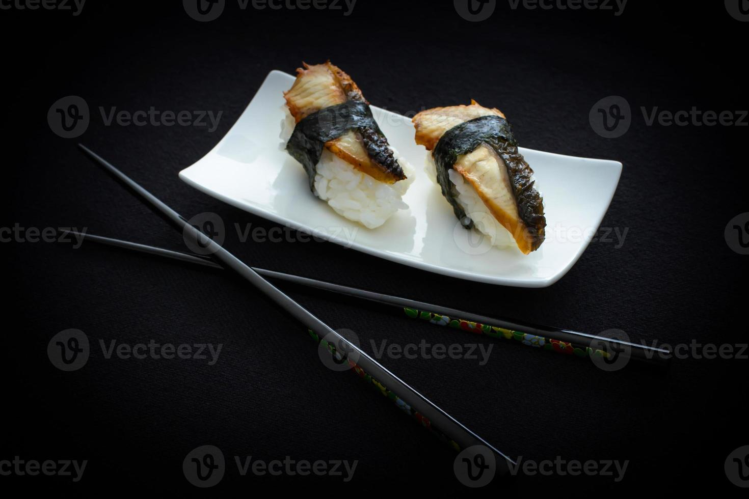 dos nigiri anguila sushi y palillos en negro foto