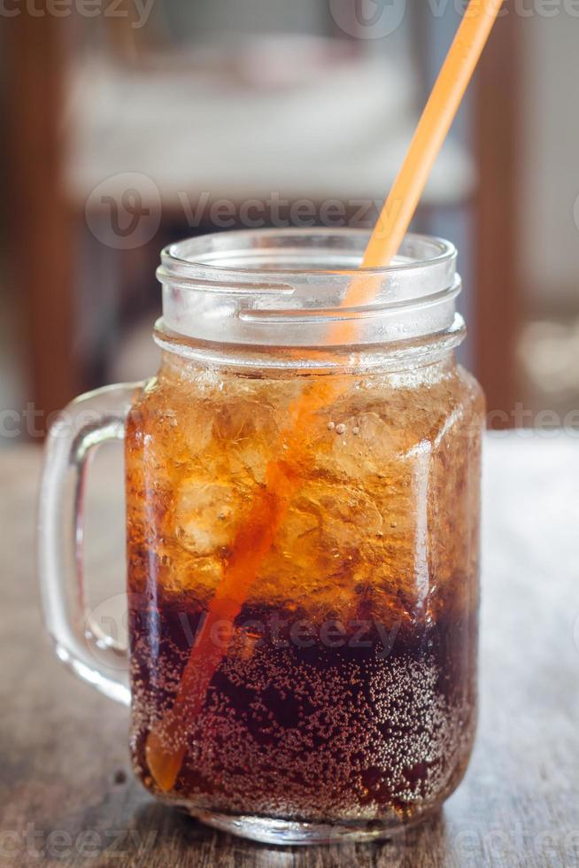 Glass of cola with ice on wooden table photo