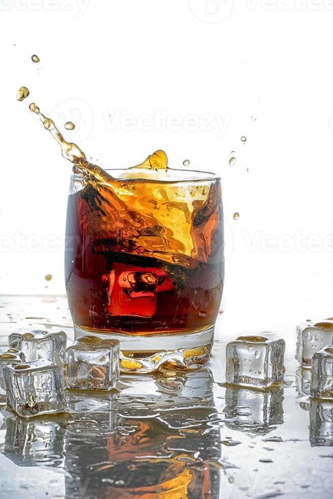 cubo de hielo caído en vaso de cola foto
