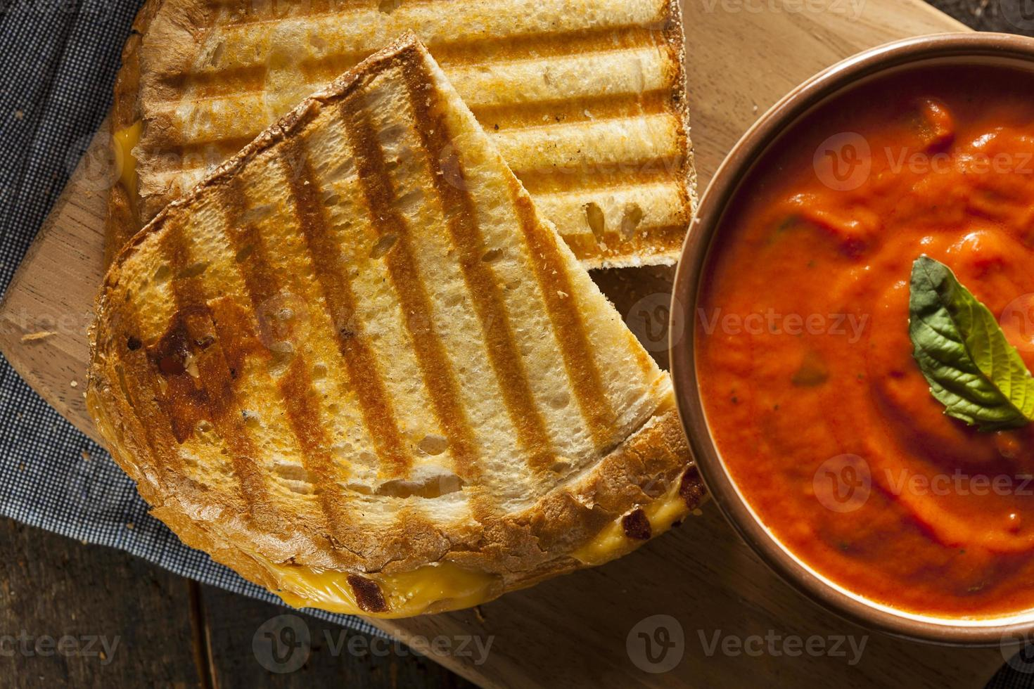 A grilled cheese sandwich with a bowl of tomato soup photo