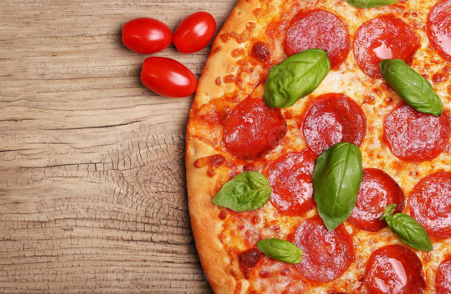Pepperoni pizza with basil and tomatoes photo