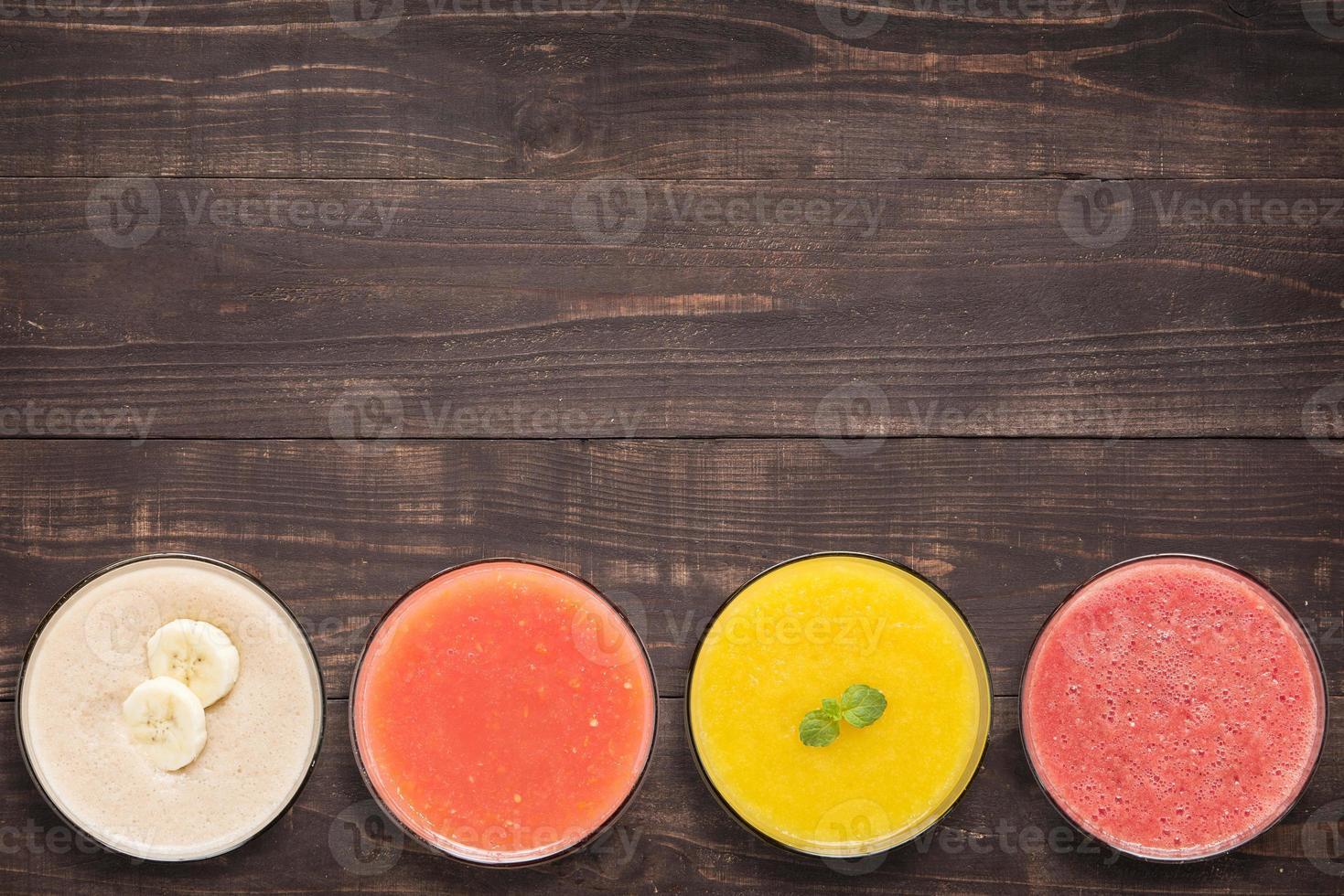 Conjunto de batido de frutas y jugo en vasos de madera foto