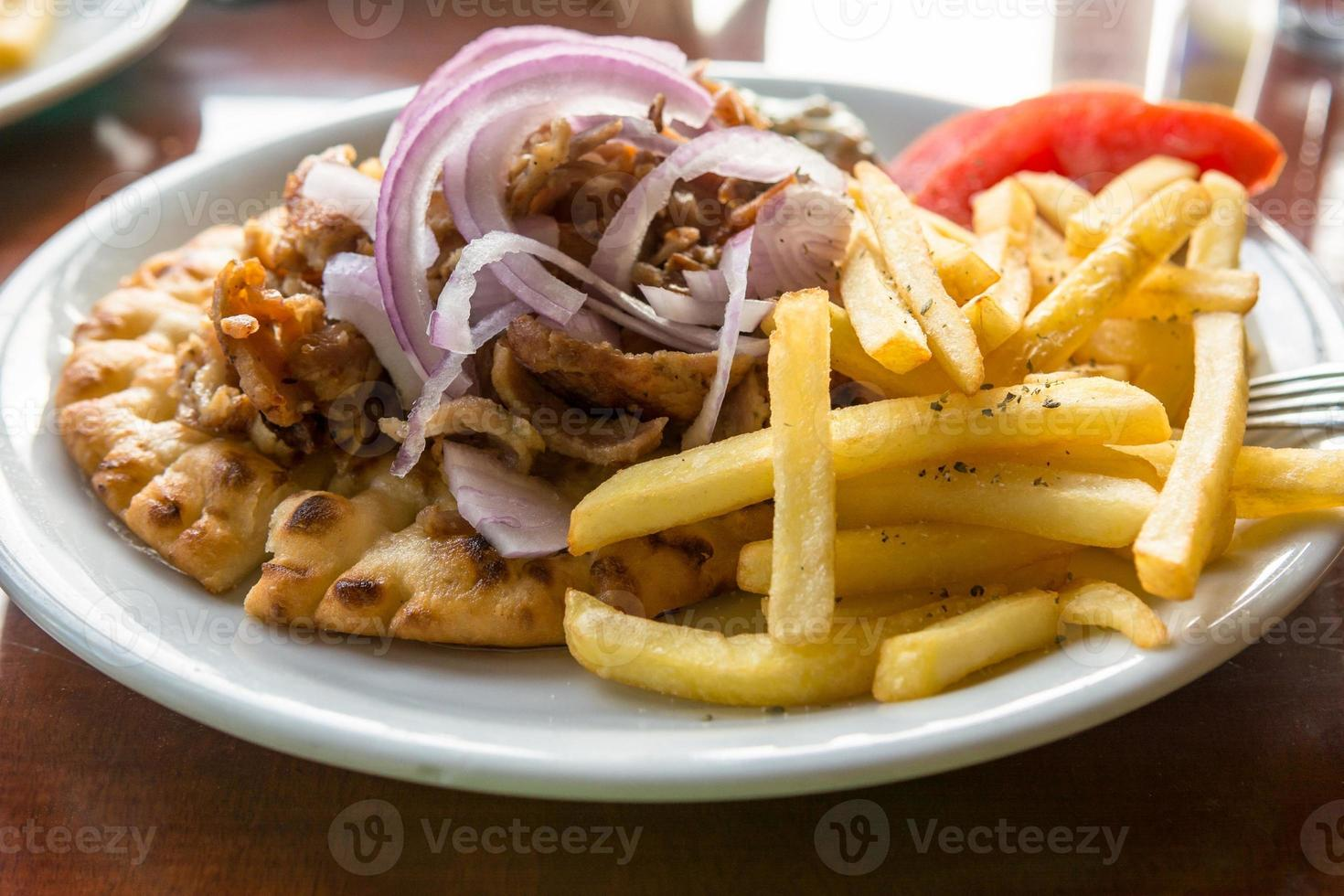 Lamb gyros with onion of fries. photo