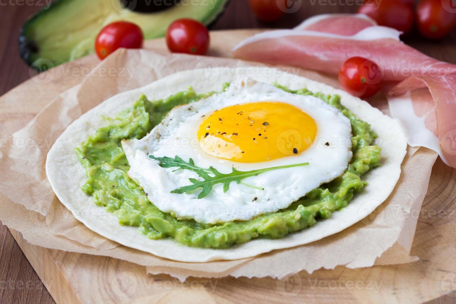 desayuno con huevo frito y salsa de aguacate sobre tortilla foto