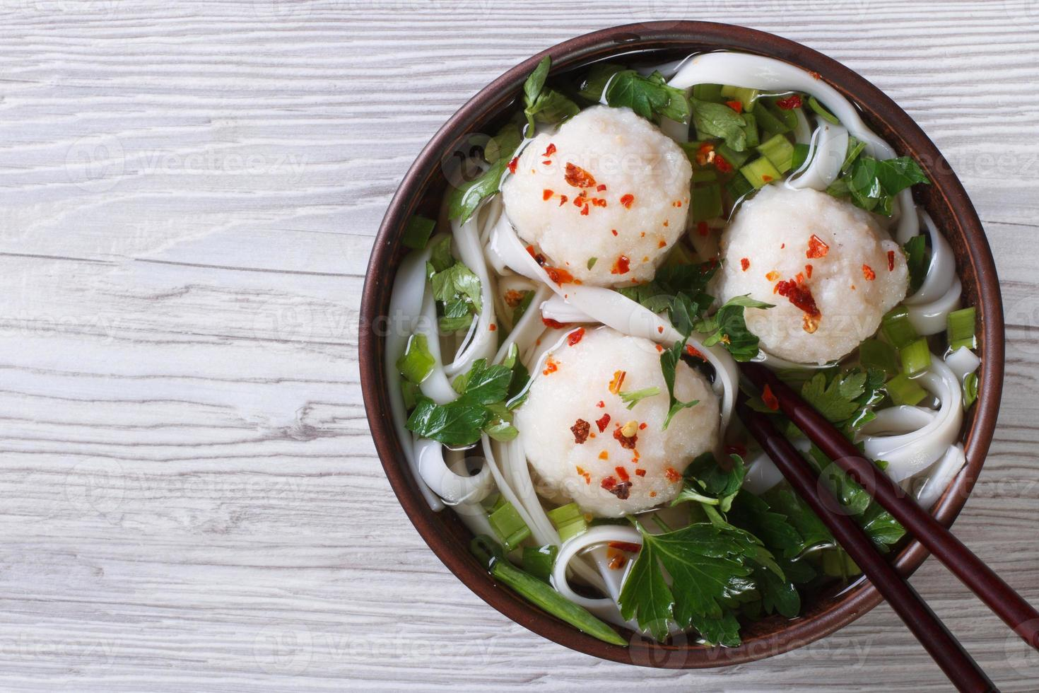 Asian soup with fish balls and rice noodles top view photo
