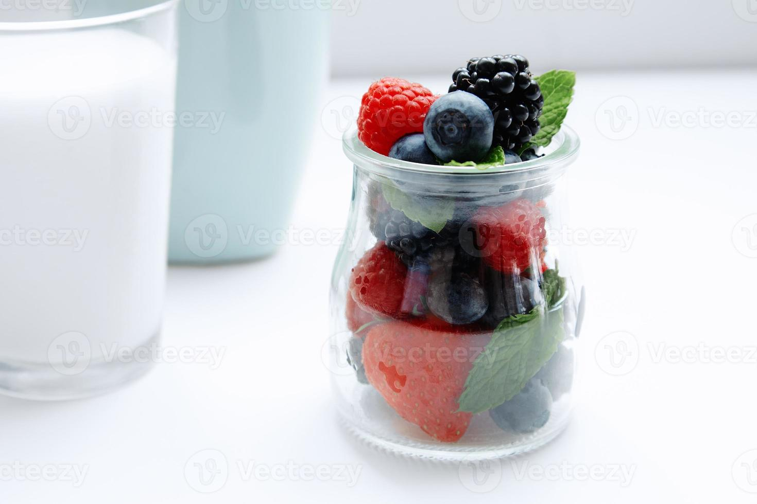 berries and mint in jar and glass of milk photo