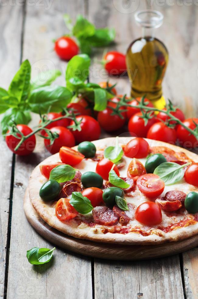 pizza italiana caliente con salami, aceituna y tomate foto