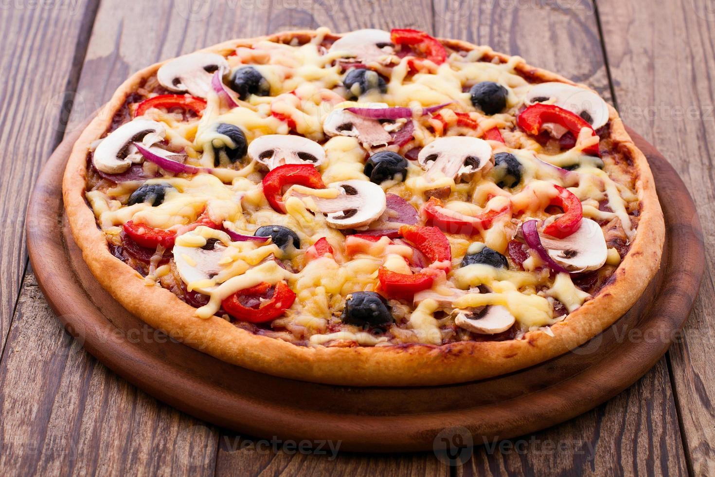 pizza con mariscos en la mesa de madera foto