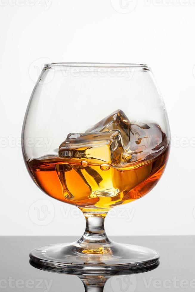 Splash de whisky con hielo en vidrio aislado en blanco foto
