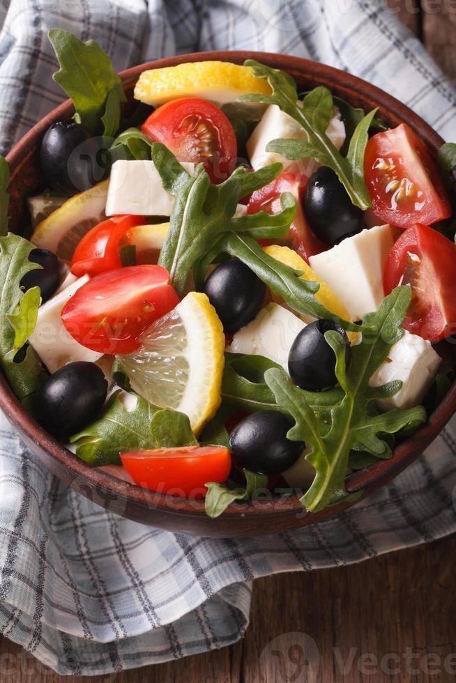 Ensalada de rúcula, queso feta, aceitunas y tomates vista superior vertical foto