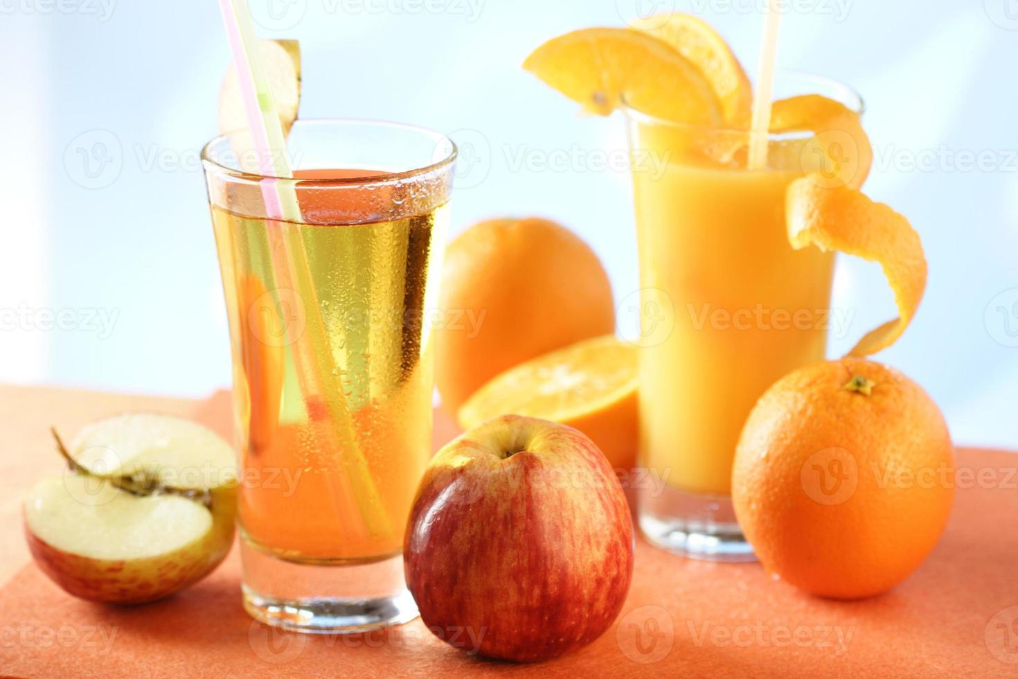 vasos de jugo de naranja y manzana con papas fritas enteras foto