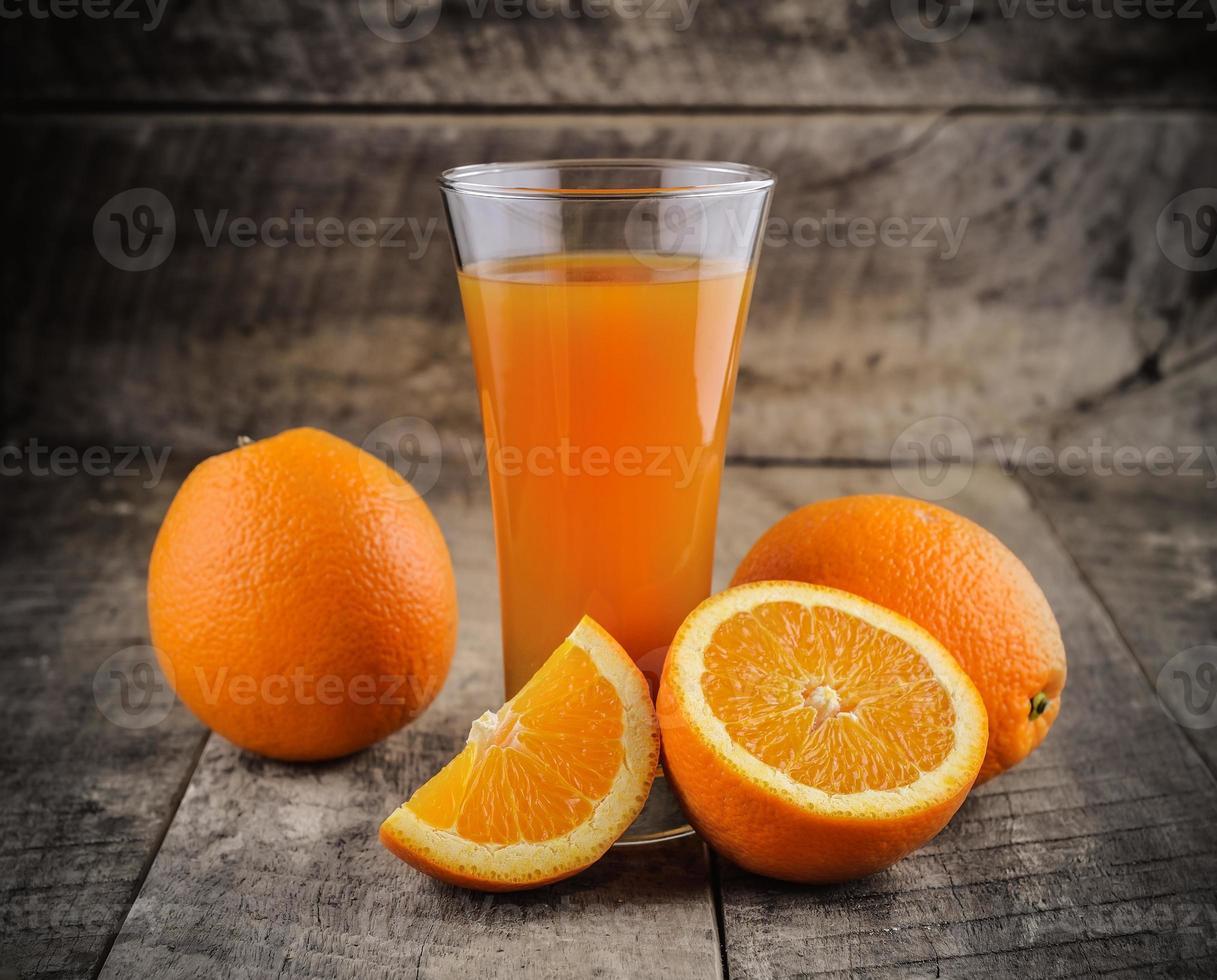 vaso de jugo de naranja y naranjas frescas en madera foto
