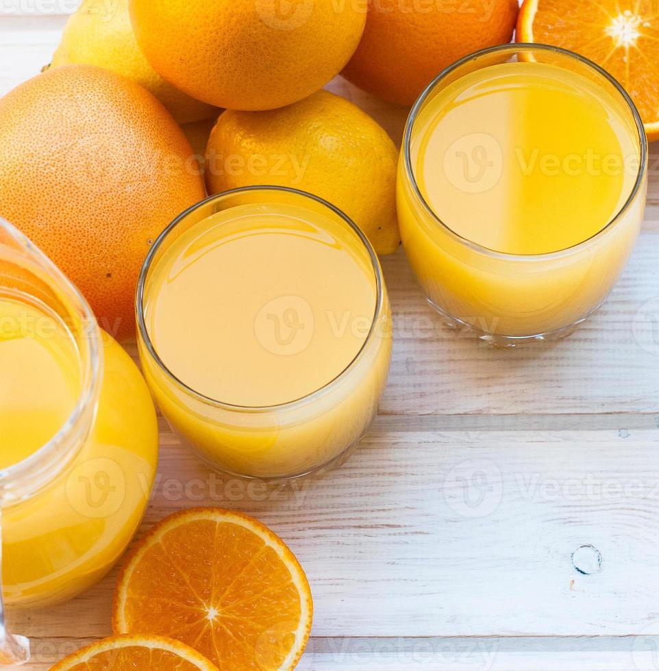 jugo de naranja fresco en mesa de madera foto