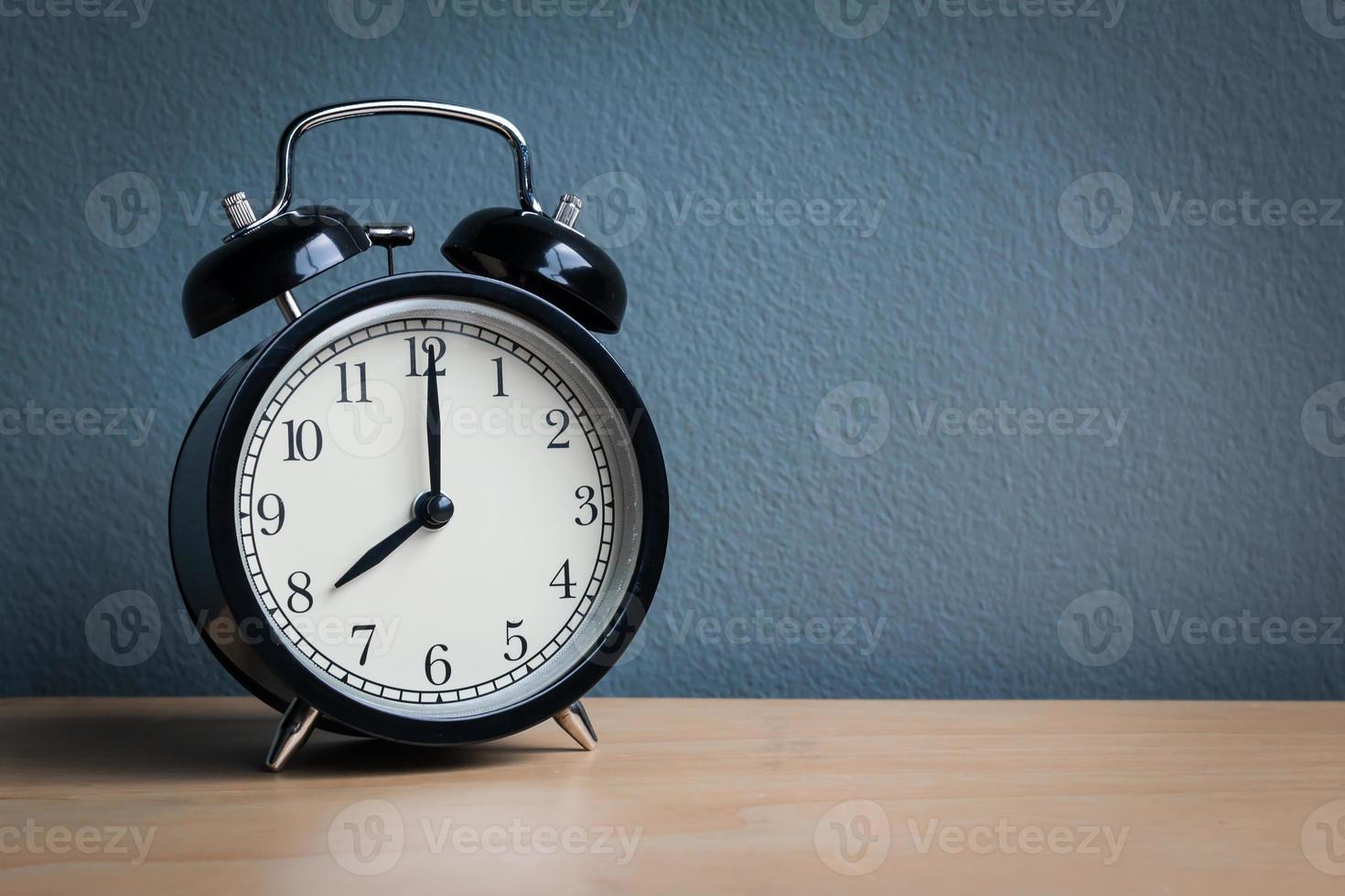 Still life with vintage alarm clock on wood table photo