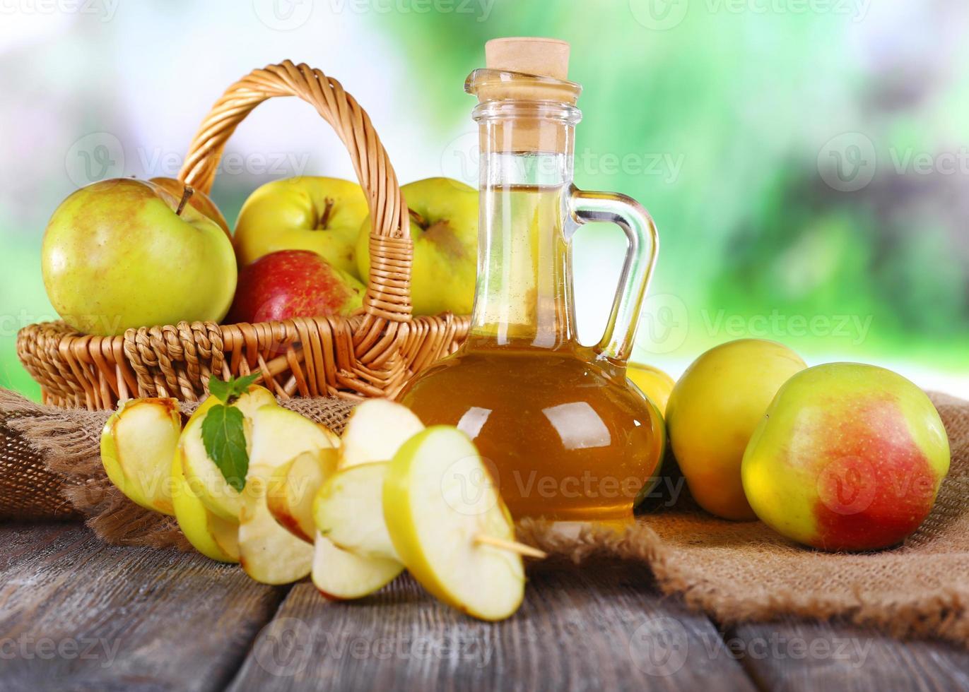 vinagre de manzana en botella y manzanas, en la mesa foto
