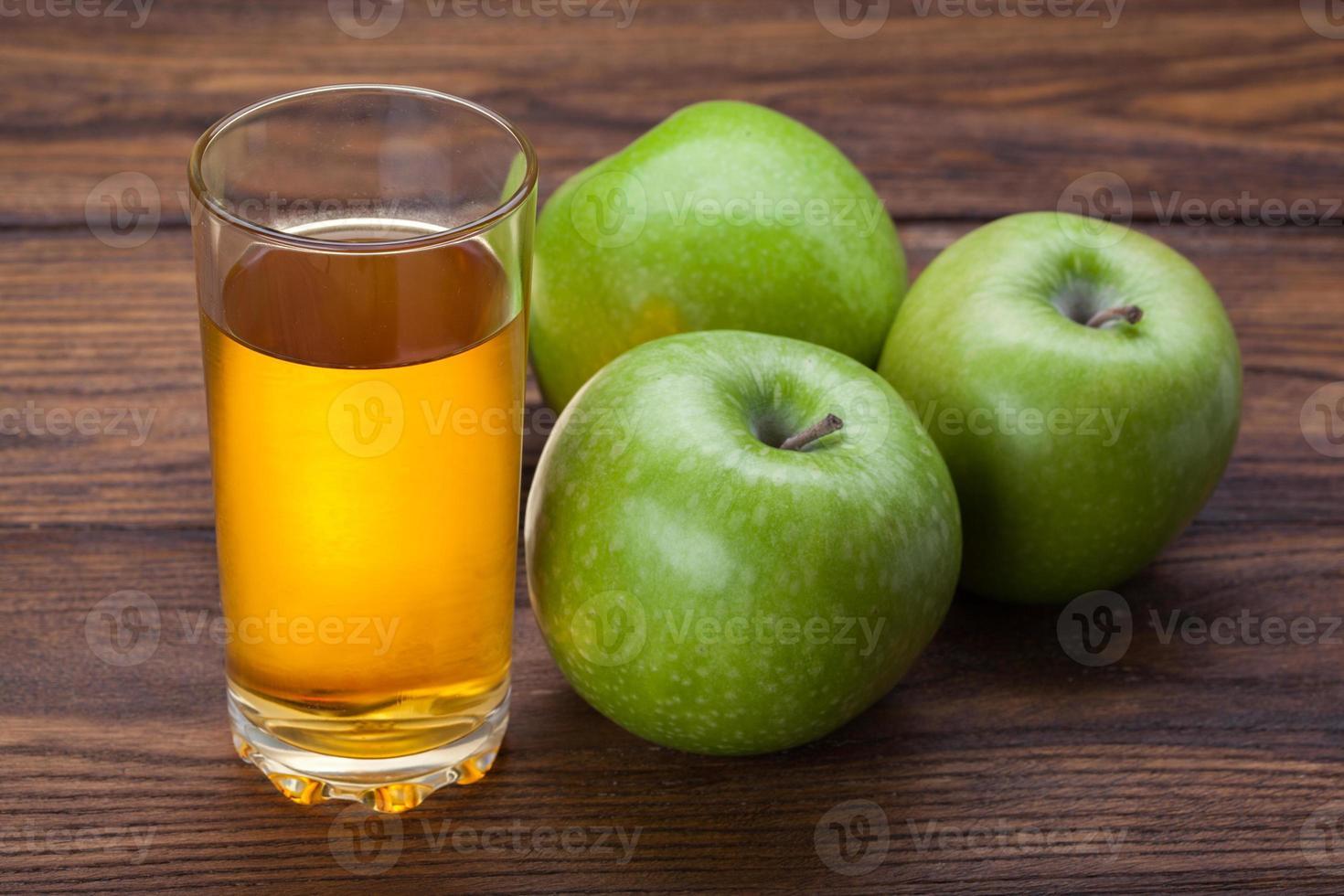 vaso de jugo de manzana y manzanas en madera foto