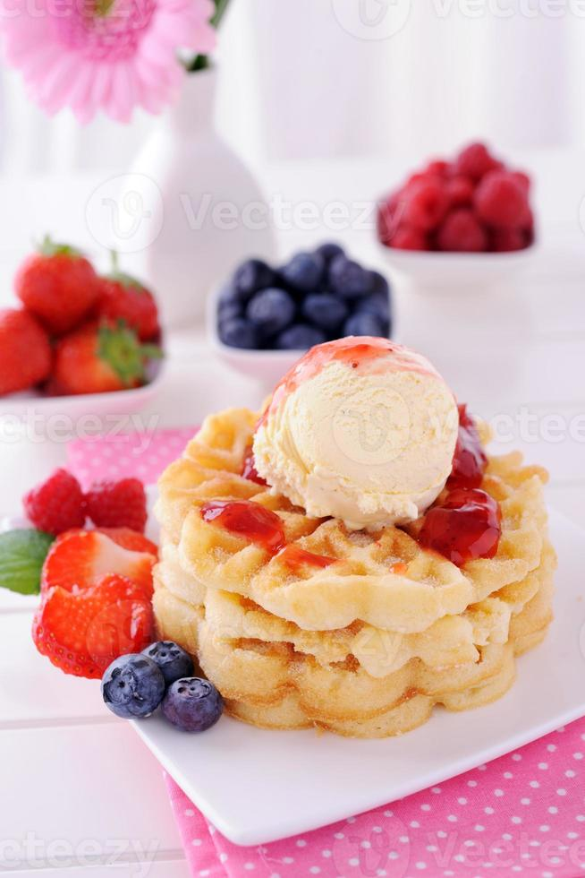Waffles with vanilla ice cream and strawberry sauce photo