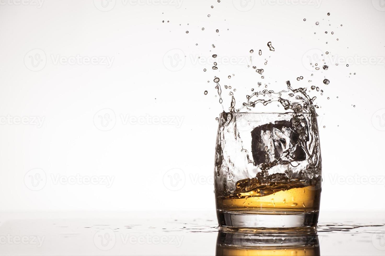 Ice splash into whiskey or brandy photo