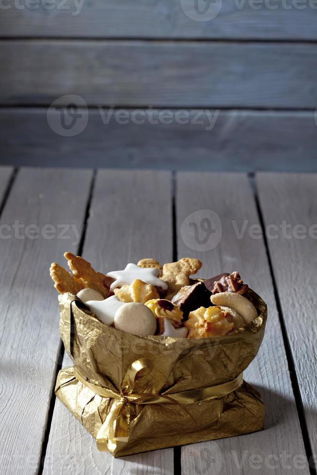 Varias galletas de Navidad en sacket dorado sobre fondo de madera foto