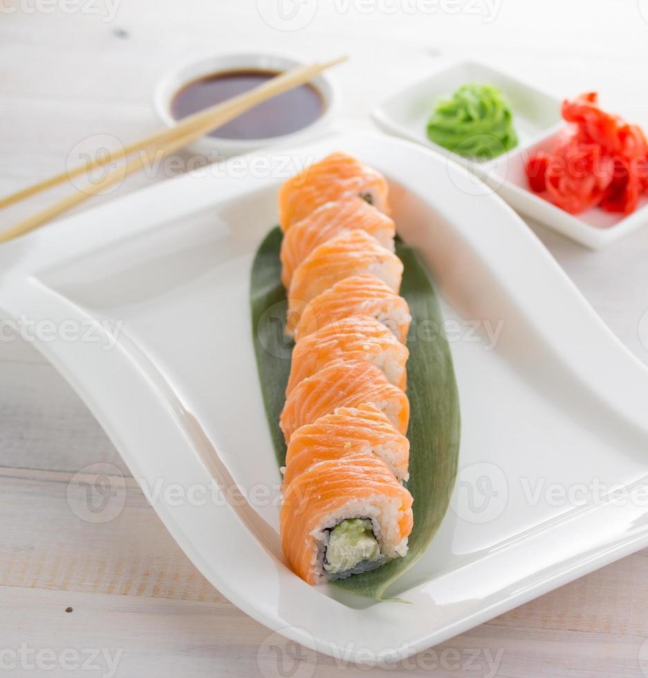 Rollo de sushi de salmón de Filadelfia en un plato sobre fondo de madera foto