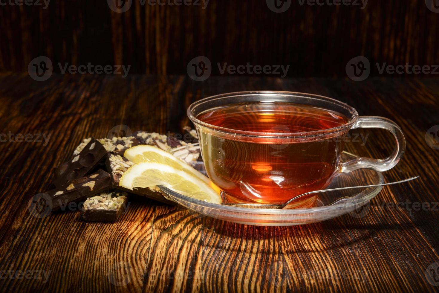taza de té con limón sobre fondo de madera foto