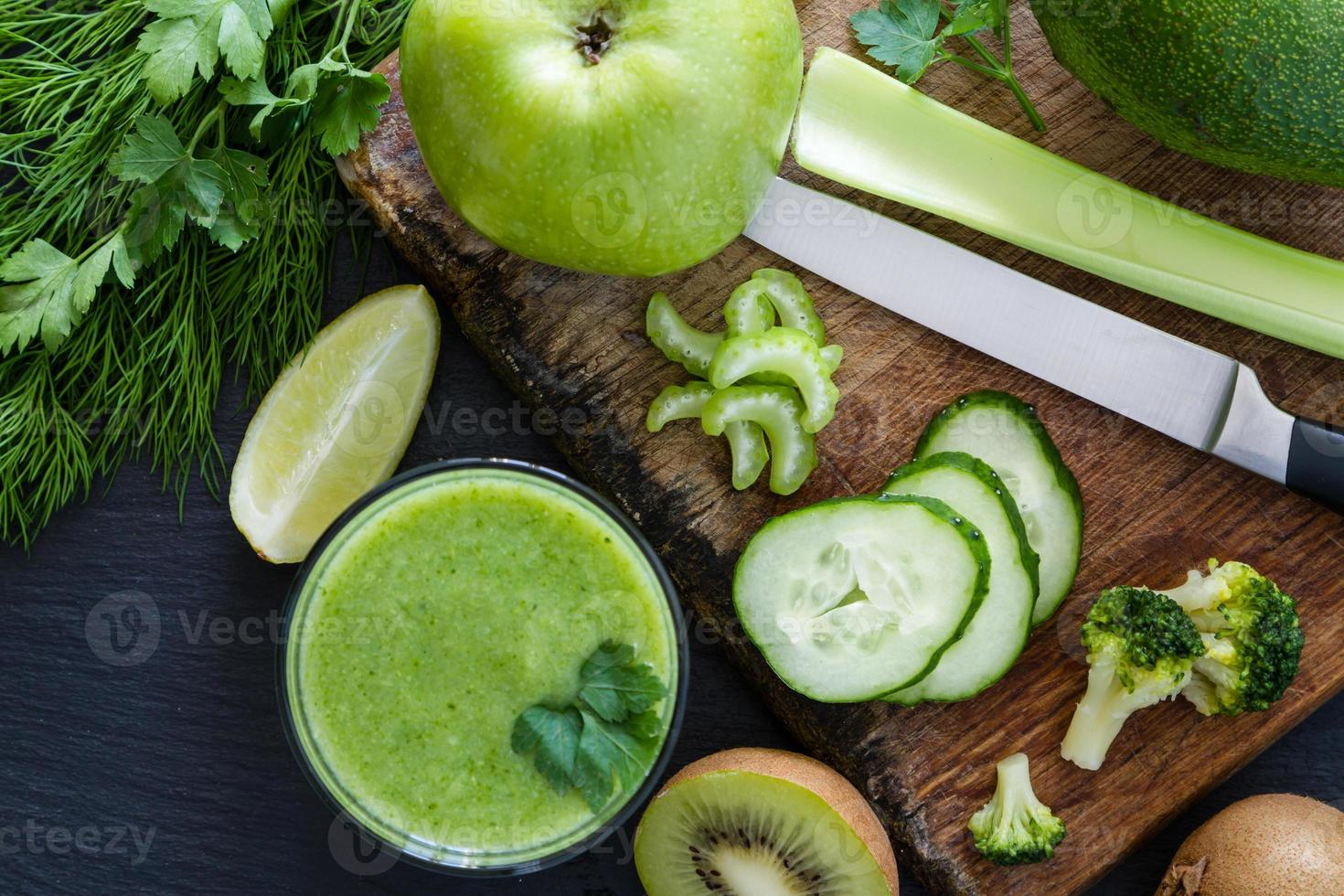 Green smoothie and ingredients - avocado, apple, cucumber, kiwi, lemon photo