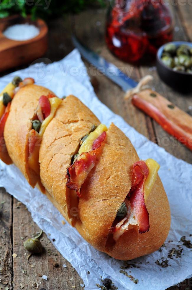 baguette al horno rellena de tocino, queso, tomates secados al sol y alcaparras foto