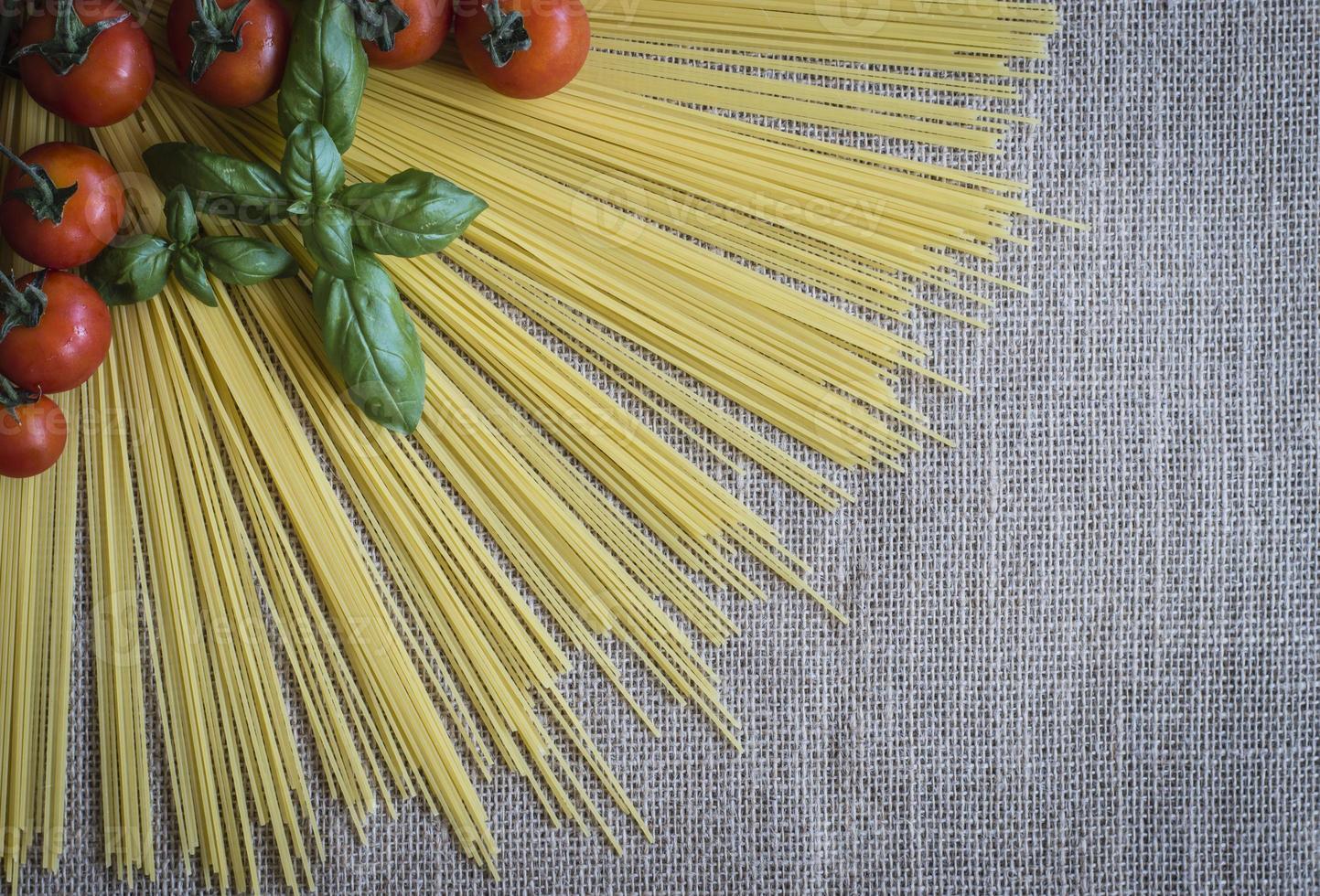 Spaghetti sunrays with cherry tomatoes and basil on jute fabric photo