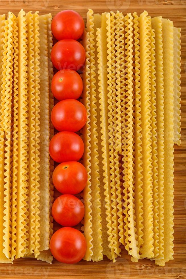 Italian pasta spaghetti and cherry tomato isolated on wooden bac photo