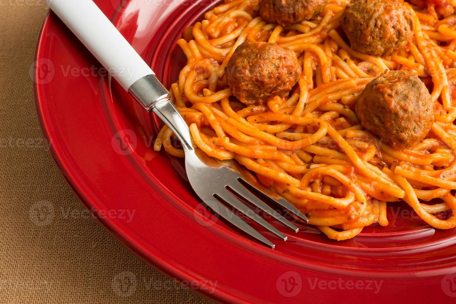 Spaghetti and meatballs on a red dish with fork. photo