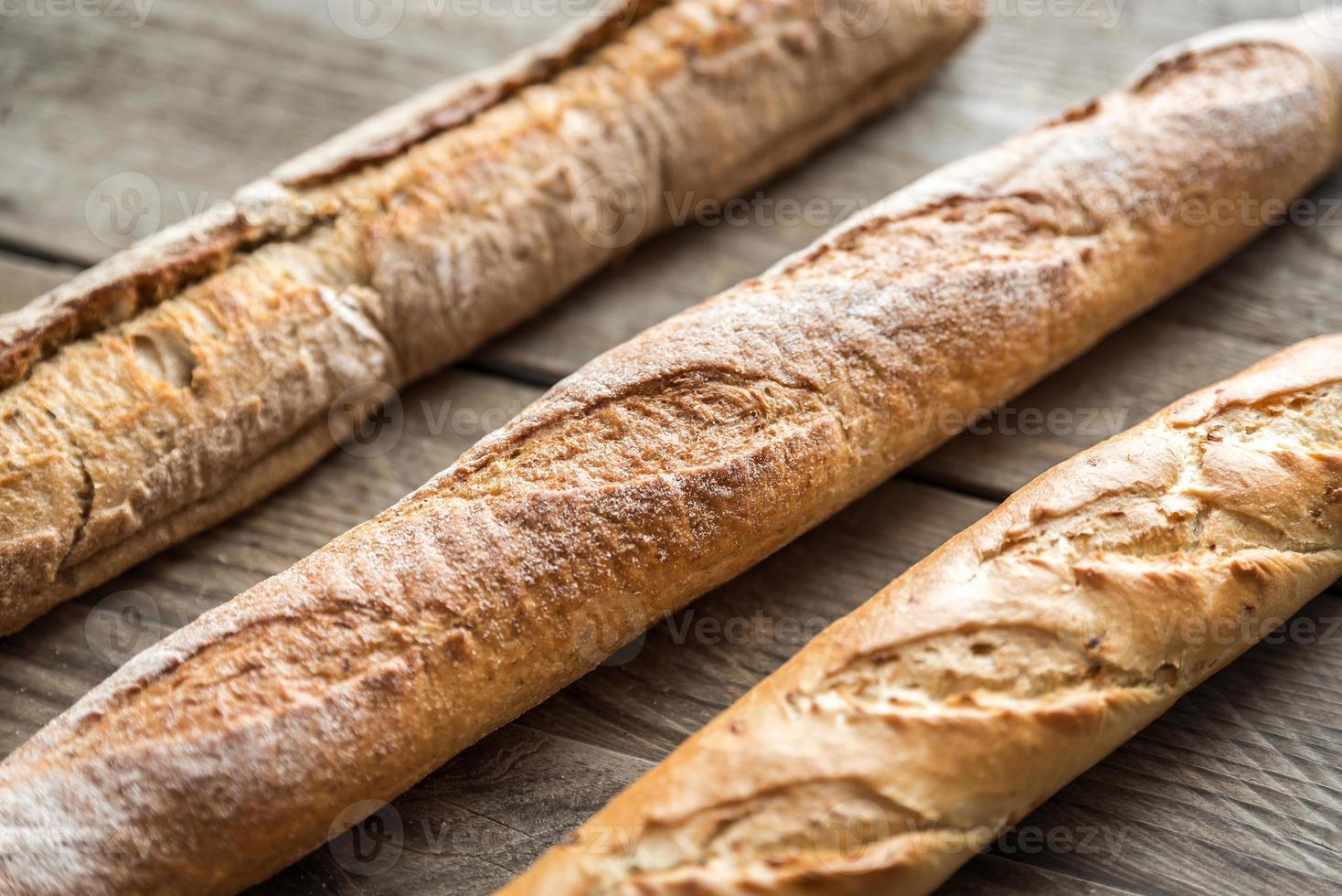 Three baguettes on the wooden background photo