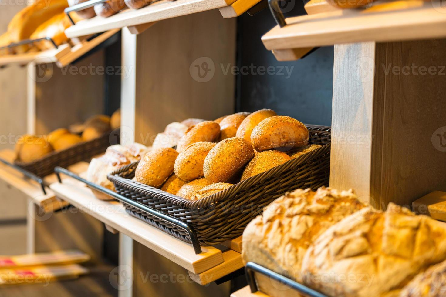 Bread and buns on shelf in bakery or baker's shop photo
