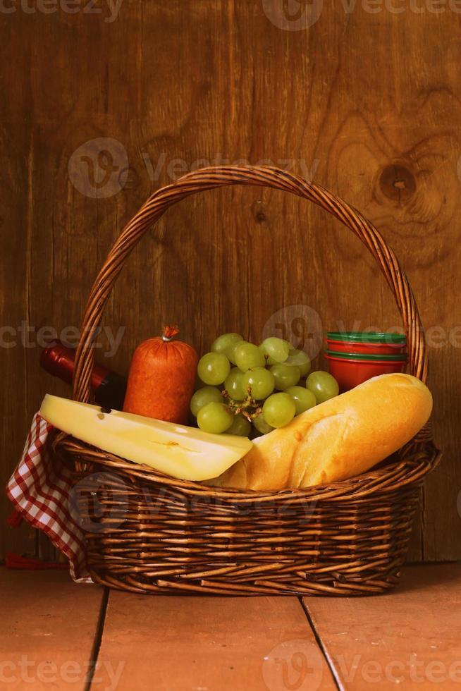cesta de picnic - vino, fruta, queso y salchichas foto