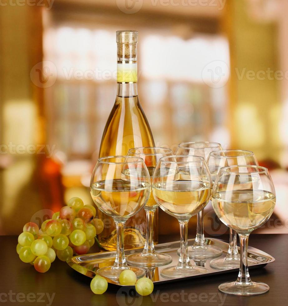 White wine in glass and bottle on room background photo