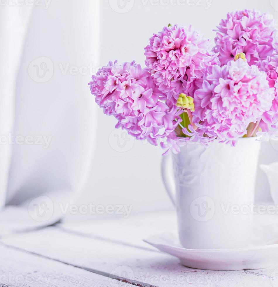Jacintos rosados en florero blanco sobre fondo blanco. foto