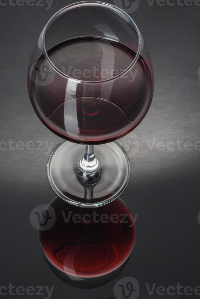 vaso lleno de vino en una mesa negra foto