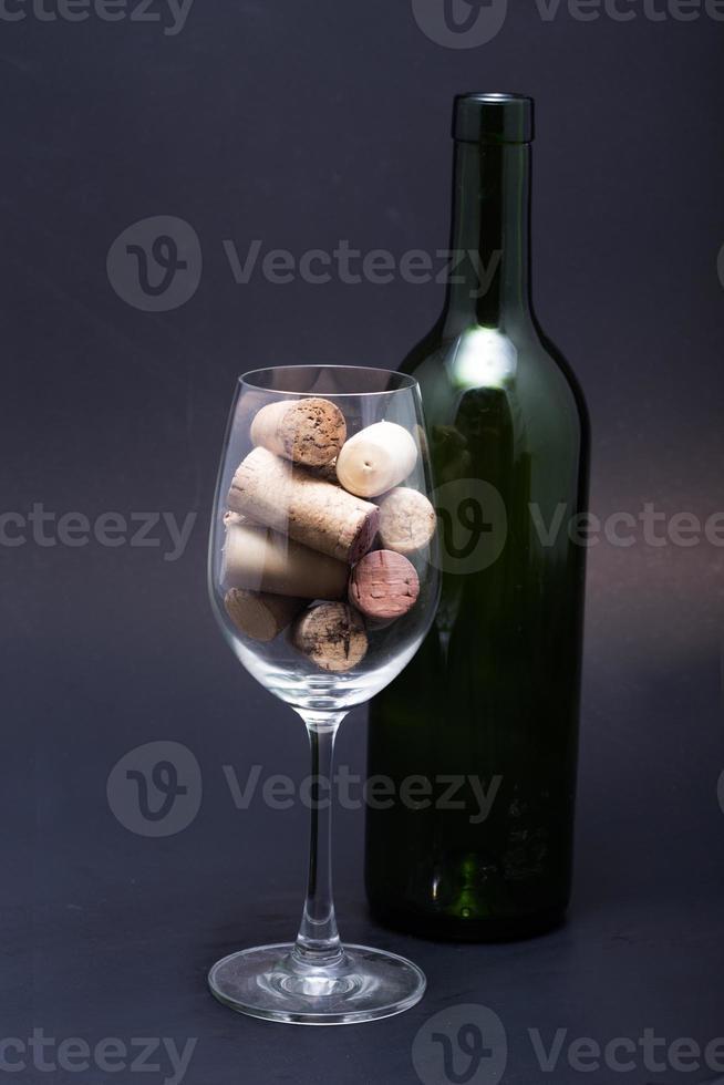 copas de vino, botellas y corchos. aislado sobre fondo negro foto