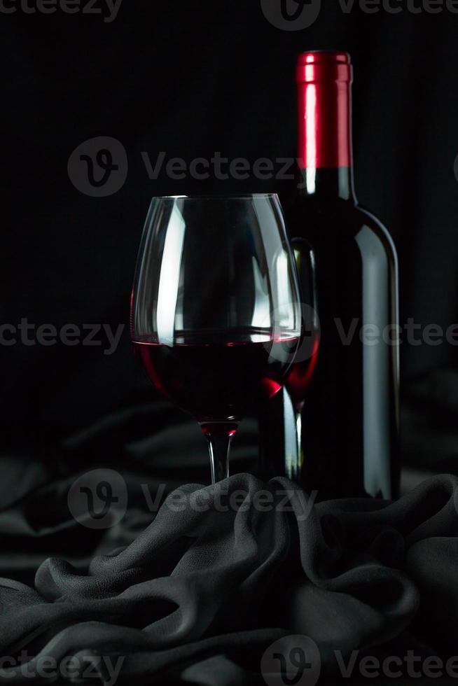 botella y vaso con rojo foto
