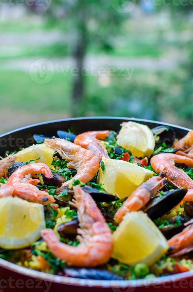 Cerrar la clásica paella de mariscos con mejillones, gambas y verduras foto