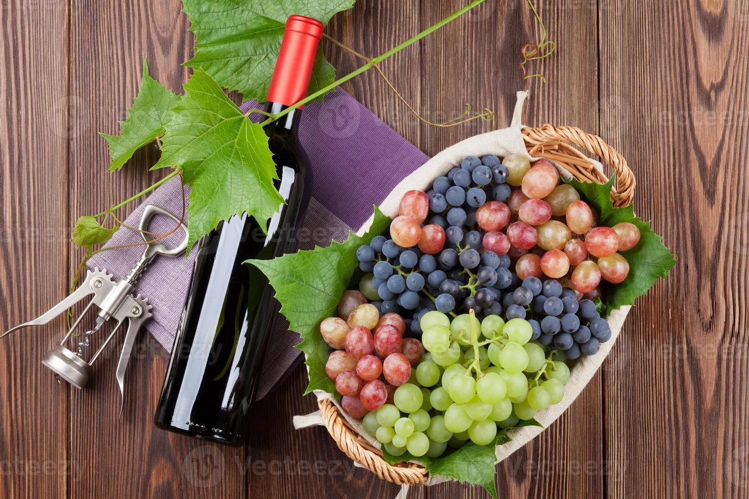botella de vino tinto y uvas coloridas foto