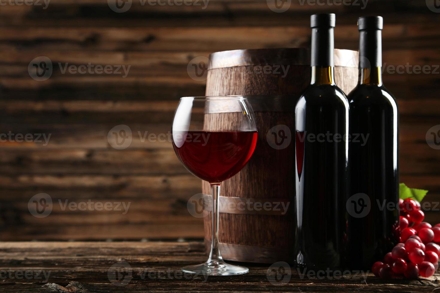 copa de vino tinto con botella y barril foto