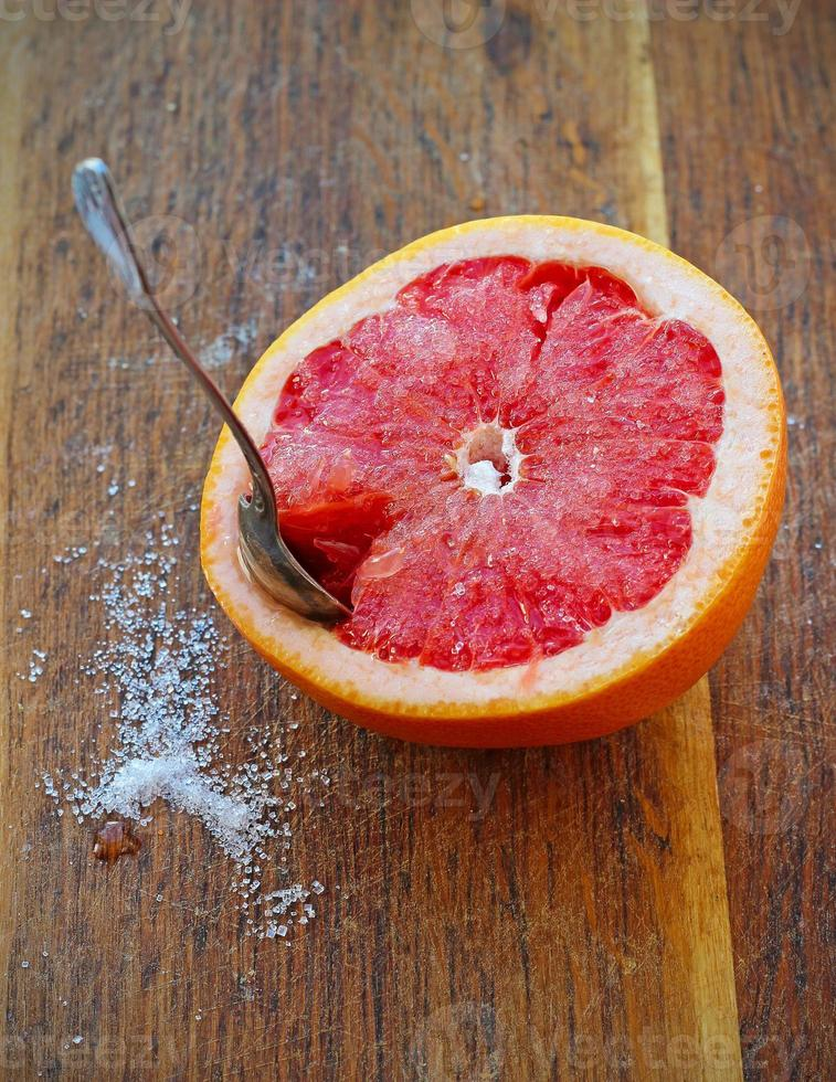 Sliced grapefruit with sugar on wooden plank photo