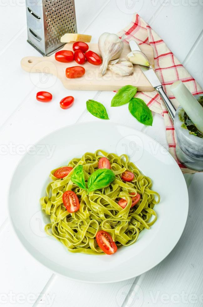 Spinach tagliatelle with basil pesto and mini tomatoes photo