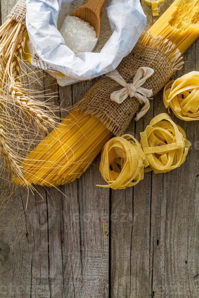 Pasta and wheat on rustic wood background photo